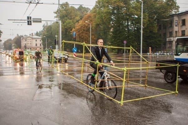 サイクリストグループは小雨ちらつく中  自動車の形状をした構造物をまとい  自転車通勤を実施した  (画像出典: Let's Bike It 公式 Facebook ページ)