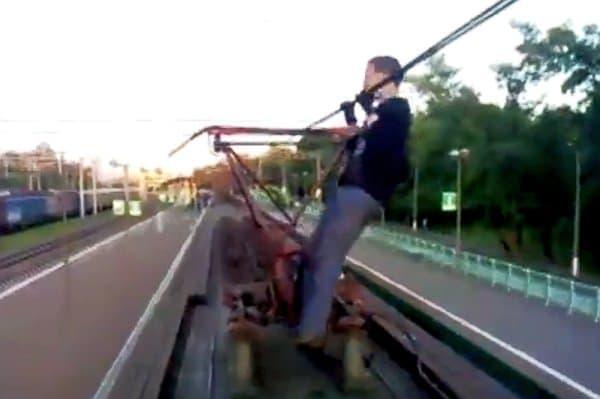悪ふざけの例:電車が停車中に、架線で懸垂をする
